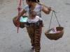 Laotisches Multitasking: Spross, Einkäufe und Schirm – alles im Gleichgewicht