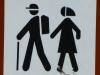 Klare Rollenverteilung: Mann mit Rucksack vorne, Frau mit Kopftuch hinten