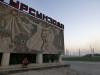 Willkommen in Tadschikistan: Vorn grüsst sozialistische Arbeiterkunst, hinten raucht fröhlich das Aluminiumwerk